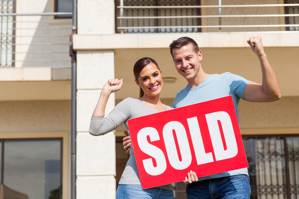 An excited couple holding a Sold sign in front of their home