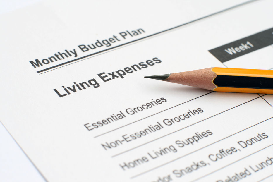 Monthly budget plan in bold text on a piece of paper with a pencil