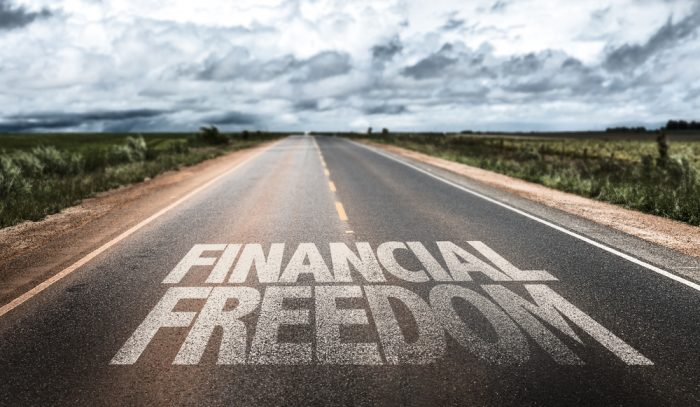 Bold white text that says Financial Freedom written on a road