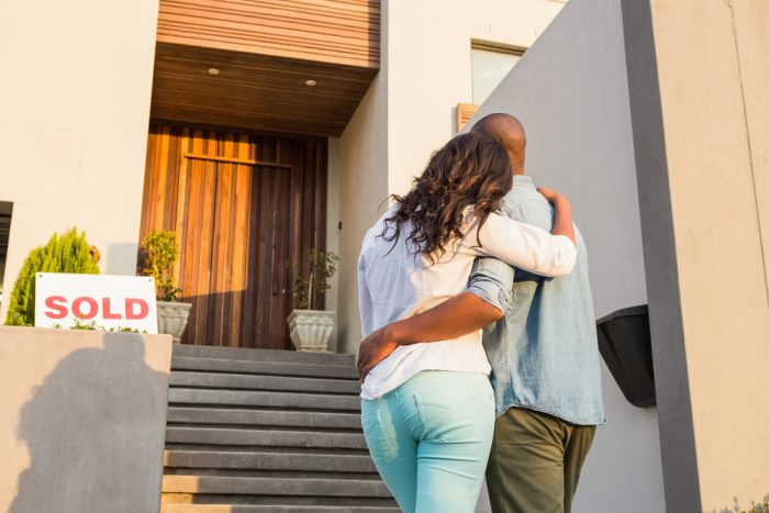 """A couple holding each other in front of their """"Sold"""" home"""