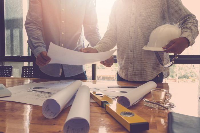 One man holding a blue print and the other is holding a white construction hat