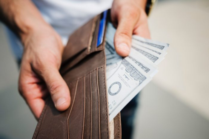 A man holding his wallet open and showing cash