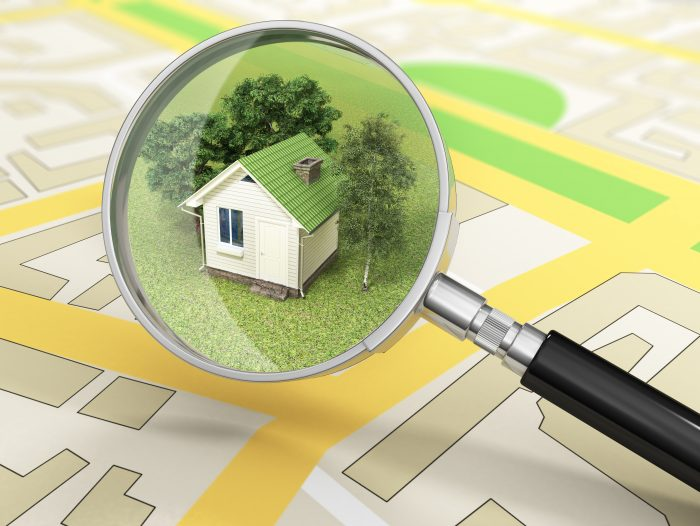 a magnifying glass with a home and trees inside